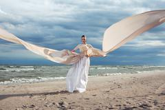 incredible portrait of model with extremely long dress at the beach. outdoors - stock photo