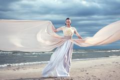 fashionable model holding a flying long dress. exclusive dress. blue sky back - stock photo