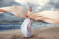 fashionable model posing in extremely long dress on the seashore - stock photo
