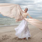 Stock Photo of female model in long beige dress posing dynamic in the beach. waving fabric.