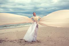 fashionable model with long beige dress like a wings - stock photo