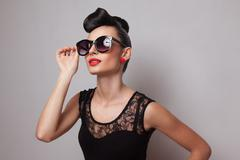 Young fashionable woman in round sunglasses posing in guipure dress. red lips Stock Photos
