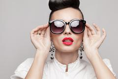 close up portrait of beautiful vintage styling model wearing round black sung - stock photo