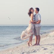 happy emotive adult couple on the sea shore.  copy space. white sand, blue wa - stock photo