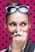 Closeup of smiling trendy girl showing mustache on pink background Stock Photos