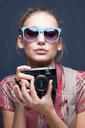 Stock Photo of trendy girl in glasses playing the ape with camera. duckface. pouting lips