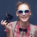 Stock Photo of smiling hipster girl with vintage camera. trendy teenager in checkered red sh