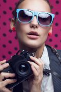 Stock Photo of close up of fashionable girl with old camera in blue sunglasses on dotted pin