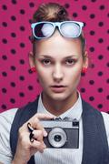 Stock Photo of fashionable teen with old camera in checkered red shirt and bow-tie.