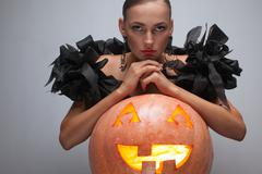 closeup shot of fashionable model in exclusive black dress sitting with pumpk - stock photo