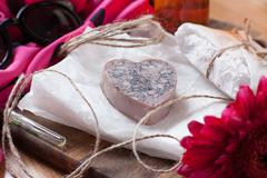 bar of homemade soap with orange and loofah. aromatized scrub soap. a heart s - stock photo