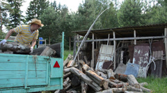 man unload tree logs firewood from trailer near woodshed house - stock footage
