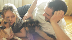Father and daughter playing on the floor with the dogs Stock Footage