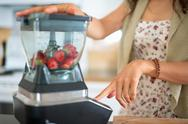Stock Photo of Health conscious woman using a blender