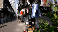 Typical Chinese old town street,china old woman leisurely sitting in a chair. Stock Footage