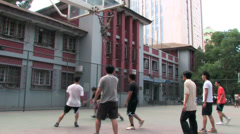 Young students playing basketball on campus Stock Footage