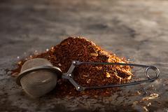 Rooibos teetä ja teetä-siivilä metalli tekstuuri Kuvituskuvat