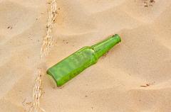 Empty green beer bottle on beach Stock Photos