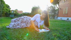 Happy pregnant woman playing with baby reading book in garden Stock Footage