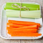 Bundle of fresh green celery stems and carrot in plate Stock Photos