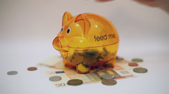 Hand insert coins in a piggy bank, counting money, savings, pension, time lapse Stock Footage