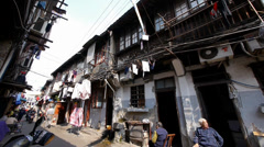 Typical Chinese old town street,china old woman leisurely sitting in a chair. - stock footage