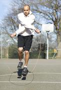 Man skipping fancily with a jump rope outdoors Stock Photos
