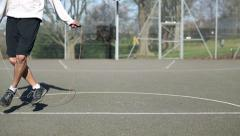 Man skipping fancily across the screen outdoors on a basketball court Stock Footage