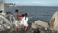 Stock Video Footage of HD Slum Kids Play On Hurricane Damaged Coastline