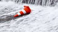Stock Video Footage of Orange traffic cone in water. Slow-motion. Stop