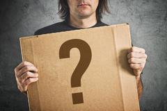 Man holding cardboard poster with question mark Stock Photos