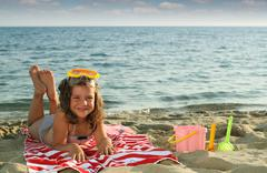 Happy little girl lying on beach summer season Stock Photos