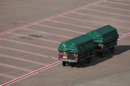 Stock Video Footage of tractors and dollies carrying luggage on dusseldorf airport apron.