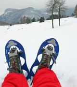 Blue snow shoes for walking on fresh snow mountain with red snow suit Stock Photos