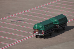 Tractors and dollies carrying luggage on dusseldorf airport apron. Stock Footage