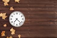 Stock Photo of clock with leaves on a brown plank