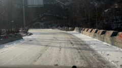 Carefully driving down the mountain road covered the snow - stock footage