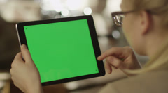 Girl Using Tablet with Green Screen in Landscape Mode in Coffee Shop Stock Footage