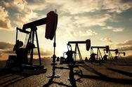 Stock Illustration of oil pumps on the sunset sky
