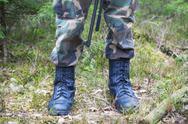 Stock Photo of Soldier's legs in army boots in a forest