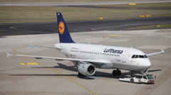 Stock Video Footage of tow tractor pushing lufthansa airbus a319-114 jet airplane d-ailm dusseldorf