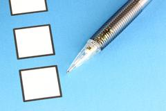 mechanical pencil point to white checkbox on blue background. - stock photo