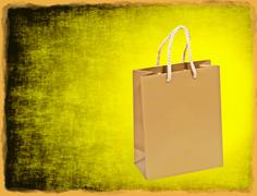 Golden shopping bag on yellow grungy background with frame border. Stock Photos