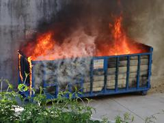 large commercial dumpster burning on fire in an alleyway - stock photo