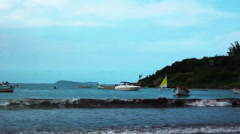 Beach at Garopaba with small waves rolling in with sailboat 2 - stock footage