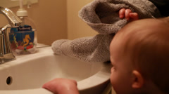 A mother helping her toddler wash hands Stock Footage