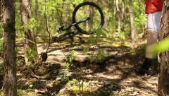 Mountain Biker hit a log in the woods and wrecks Stock Footage