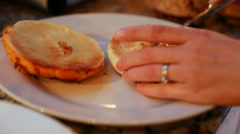 A woman putting cream cheese on a toasted bagel Stock Footage