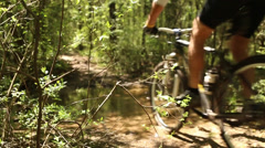 Mountain bike thru creek in the woods - stock footage