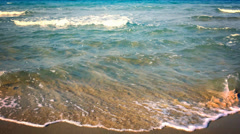 Sea waves on sand beach of tropical island at sunset. Clear blue ocean water 4K - stock footage